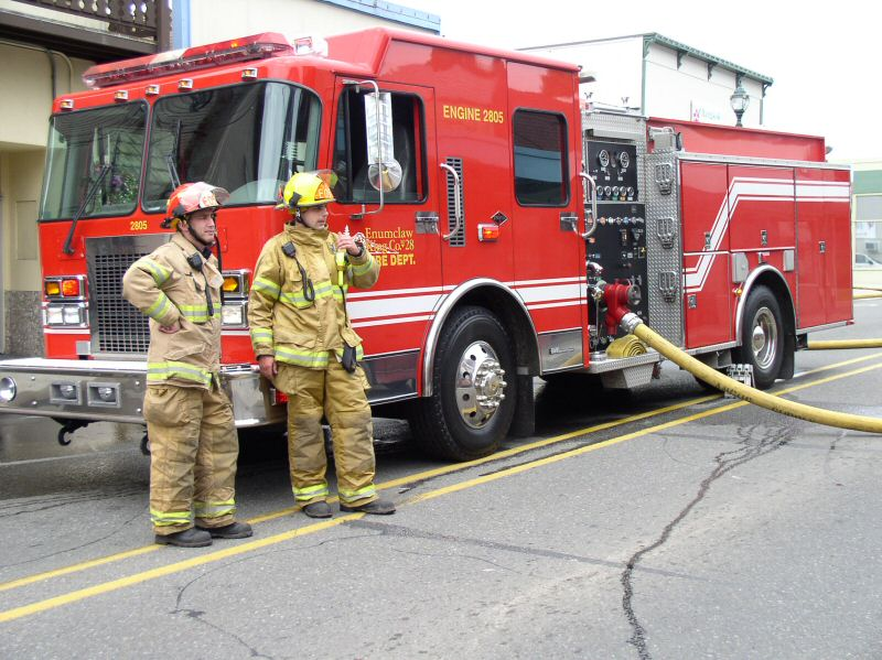 Firefighters stand by their fire engine
